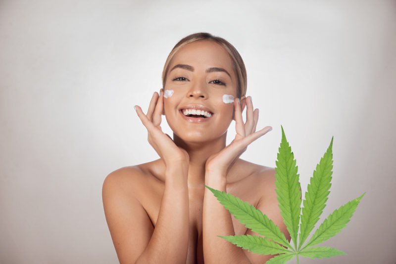 Brunette woman applying CBD facial cream made from cannabis extract for a natural cbd skincare treatment. Portrait of young woman with cannabis leaf. Cosmetology and treatment concept. Isolated on gray background