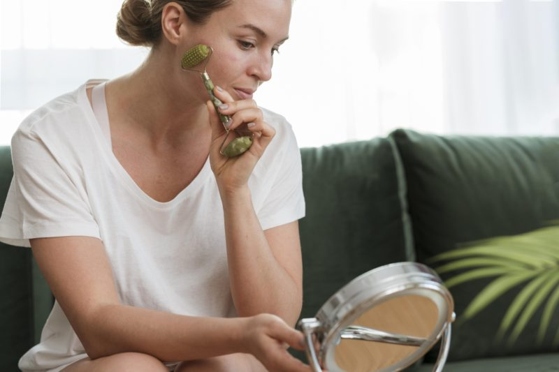 woman using face massage tool selfcare concept